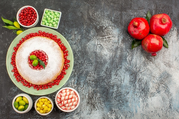 Kuchen und süßigkeiten ein appetitlicher kuchen schalen mit süßigkeiten limetten drei granatäpfel