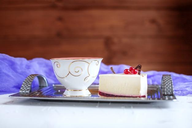 Kuchen und tee auf einem tablett auf einem hölzernen hintergrund. das konzept von fo