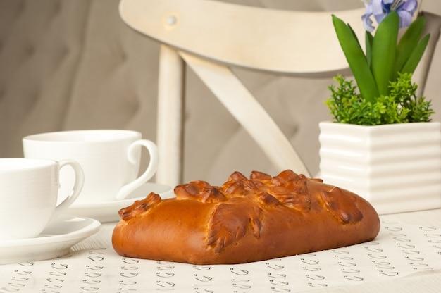 Kuchen und zwei tassen kaffee auf einem tisch mit blumen auf dem hintergrund des stuhls