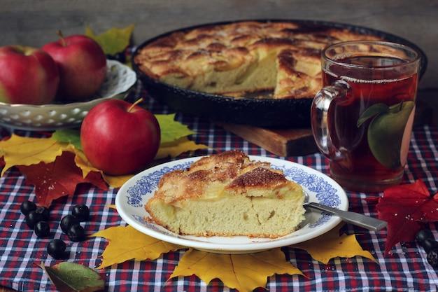 Kuchen von äpfeln. charlotte. ein stück kuchen auf einer platte, einer teeschale und roten äpfeln