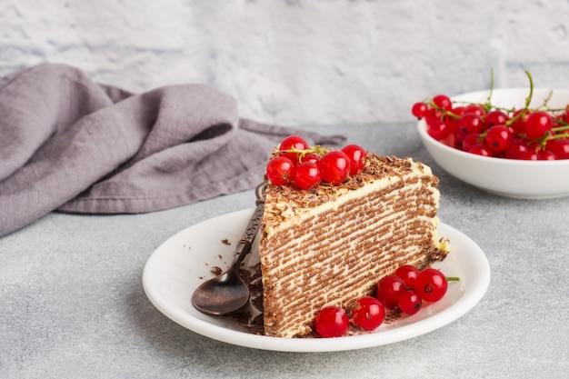 Kuchen von dünnen schokoladenpfannkuchen und pistaziencreme mit roten johannisbeerbeeren