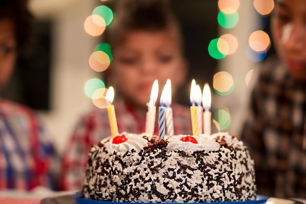 Kuchen vor jungenkuchen und kinder auf hintergrundgeburtstagstisch im dekorierten raum feiern mit ...