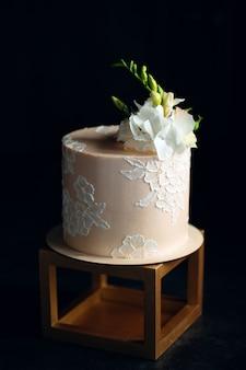 Kuchen wird mit blumen auf dunkelheit verziert