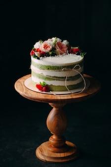 Kuchen wird mit blumen auf einer dunkelheit verziert.