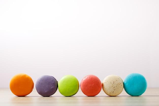 Kuchenmakronen oder makronen auf pastellfarbenem hintergrund mit kopierraum, süßem und buntem dessert