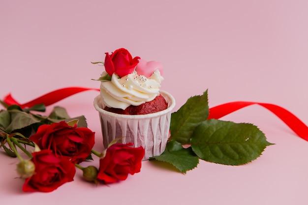 Kuchenrosen und -herzen auf einem rosa. schokoladenkleine kuchen verziert mit sahnerose