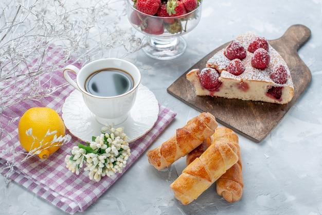 Kuchenscheibe mit frischen roten erdbeeren, süßen armreifen und einer tasse kaffee auf hellem schreibtisch, süßes backkeks-keksgebäck