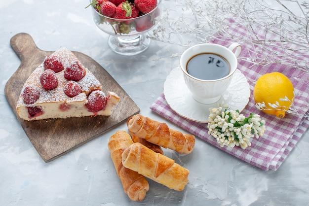Kuchenscheibe mit frischen roten erdbeeren, süßen armreifen und kaffee auf hellem schreibtisch, süßes backkeks-keks-tee-gebäck