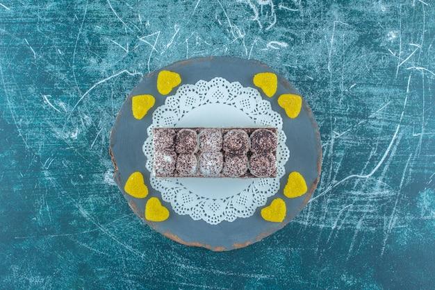 Kuchenscheibe und marmeladen auf einem holzbrett auf blauem hintergrund. hochwertiges foto