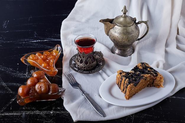 Kuchenscheiben in einem weißen teller mit schokoladensirup und tee.