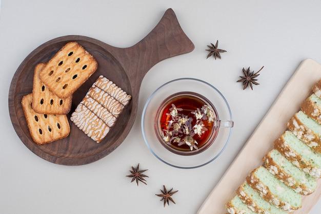 Kuchenscheiben, kekse und eine tasse tee auf weiß.