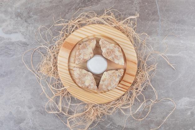 Kuchenscheiben um einen mit vanillepulver beschichteten keks auf einem holzteller auf marmor