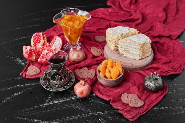 Kuchenscheiben und konfekt auf rotem handtuch mit tee.
