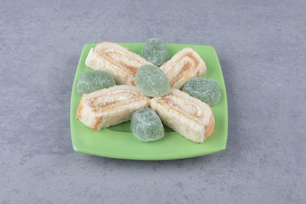 Kuchenscheiben und marmeladen auf einer grünen platte auf marmor `