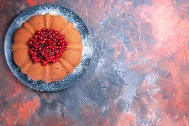 Kuchenteller mit appetitlichem kuchen und roten johannisbeeren auf dem rot-blauen tisch