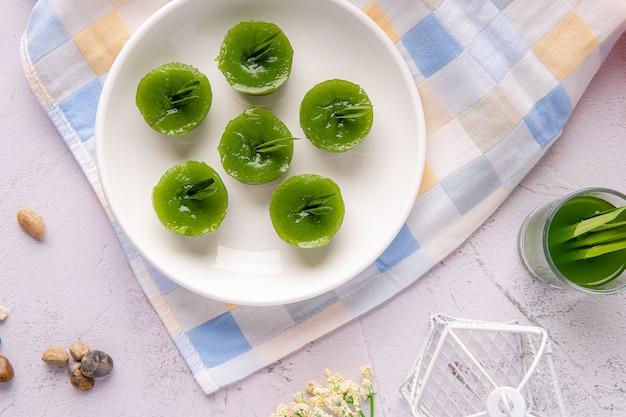 Kue lumpang pandan oder kue ijo kue ijo ist ein traditioneller grüner kuchen und ist klein gedämpft und hat eine gummiartige textur, die mit geriebener kokosnuss serviert wird