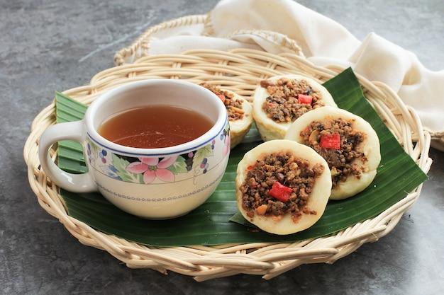 Kue talam oncom, traditioneller gedämpfter cup cake aus indonesien mit oncom topping. oncom ist ein traditionelles grundnahrungsmittel aus west java, das aus sojabohnen- oder erdnussfermentation hergestellt wird. bekanntes kuih talam malaysia