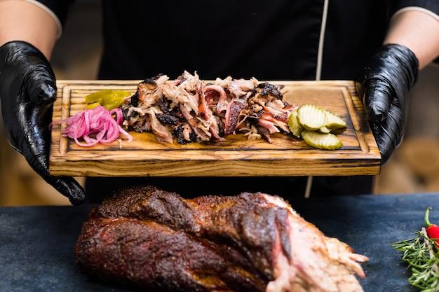 Küche des grillrestaurants. kochhände in schwarzen kochhandschuhen, die geräuchertes schweinefleisch mit gurken auf holzbrett halten.