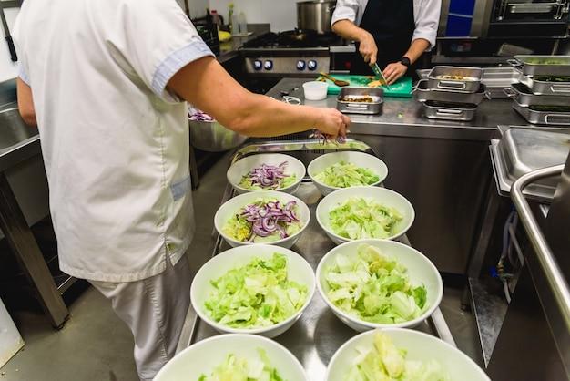 Küche eines restaurants, während die köche einen salat vorbereiten.