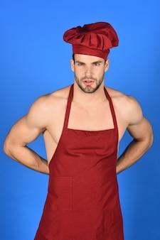 Küche und kochkonzept sexy mann in burgunderrotem hut und schürze attraktiver koch in köchen gekleidet