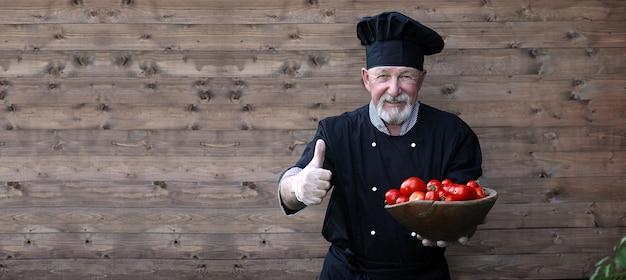 Küchenchef alt in uniform mit frischem gemüse auf einem hölzernen hintergrund