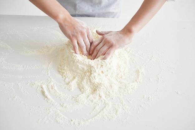 Küchenchef, der mit mehlteig arbeitet, der serviceküchenprofi macht