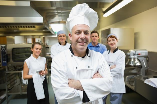 Küchenchef, der mit team hinter ihm aufwirft