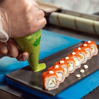 Küchenchef gießt wasabi auf den sushi-tisch, california unagi sushi roll