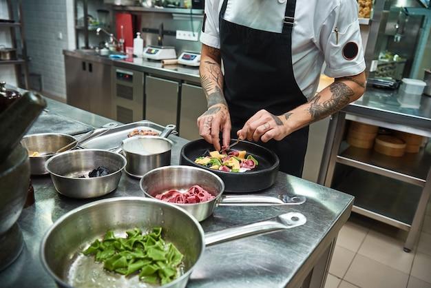 Küchenchef hände garnieren italienische pasta auf dem teller in einer restaurantküche