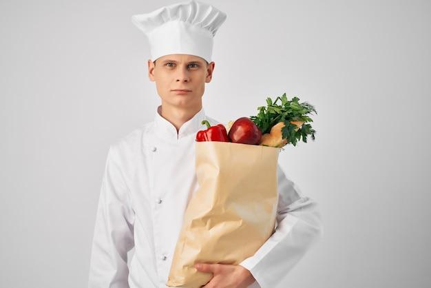 Küchenchef mit paket frischer lebensmittel-restaurant-lieferarbeiten