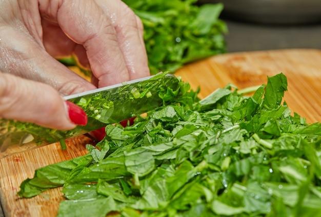 Küchenchef schneidet basilikum nach dem rezept zum kochen auf holzbrett in der küche.