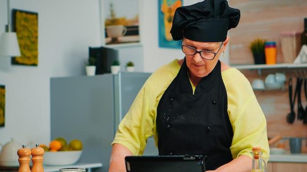 Küchenchefin mit tablet in der küche beim pizzakochen. pensionierte dame, die kulinarischen ratschlägen auf dem laptop folgt, ein koch-tutorial in den sozialen medien lernt und den teig mit einem hölzernen nudelholz formt.