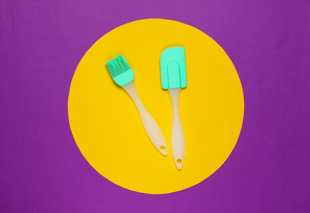 Küchengeräte auf lila mit einem gelben kreis in der mitte