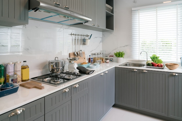 Küchengeräte aus holz, kochzubehör. hängende kupferne küche mit weißer fliesenwand.