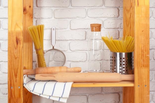 Küchengeräte und dishware auf hölzernem regal