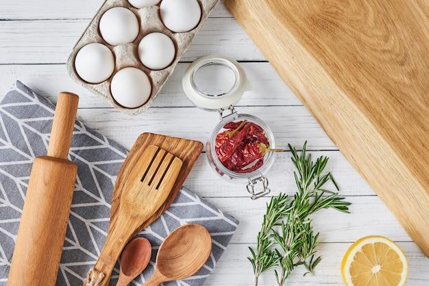 Küchengeräte und kochen von bestandteilen auf einem weißen hölzernen hintergrund, draufsicht