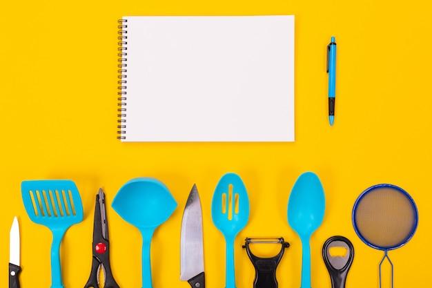 Küchengeräte und sauberes blatt papier lokalisiert auf gelbem hintergrund