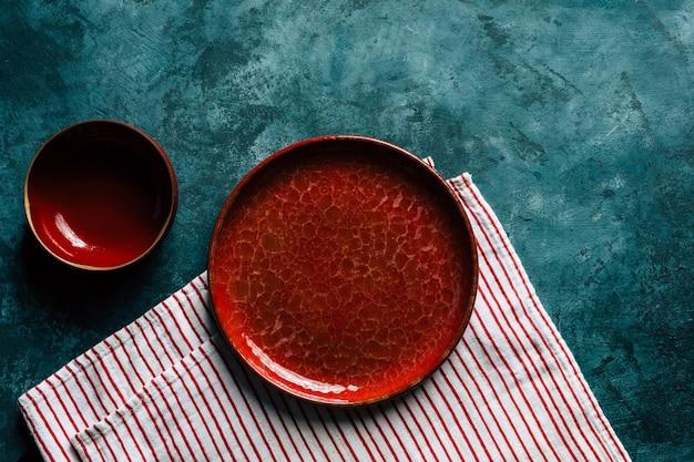Küchenhintergrund rote keramikplatte auf blauem hintergrund