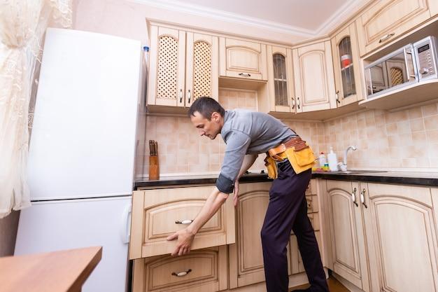 Kücheninstallation. arbeiter, der möbel zusammenbaut.
