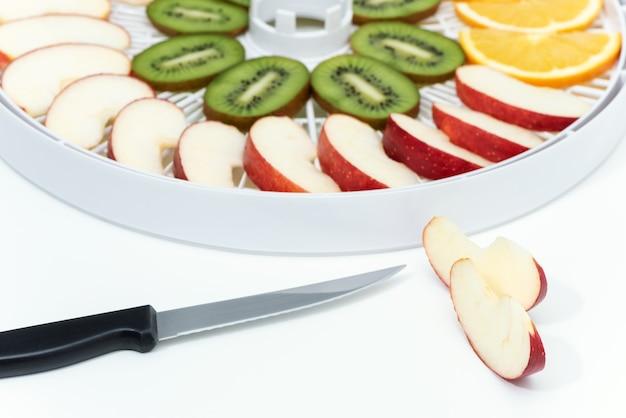 Küchenmesser und apfel schneiden. dahinter befindet sich ein tablett mit einem dörrgerät mit kiwi- und apfelscheiben.