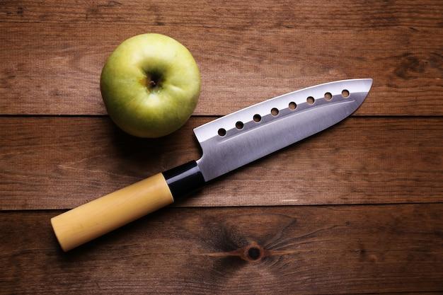 Küchenmesser und grüner apfel auf holztisch