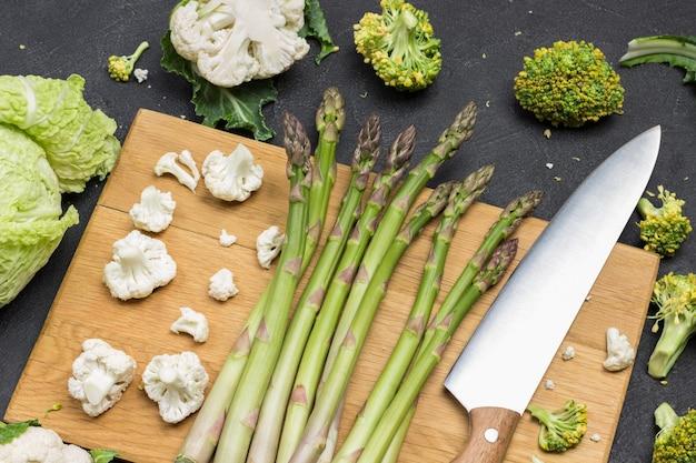 Küchenmesser und spargel auf schneidebrett. blumenkohl und brokkoli auf dem tisch. schwarzer hintergrund. ansicht von oben