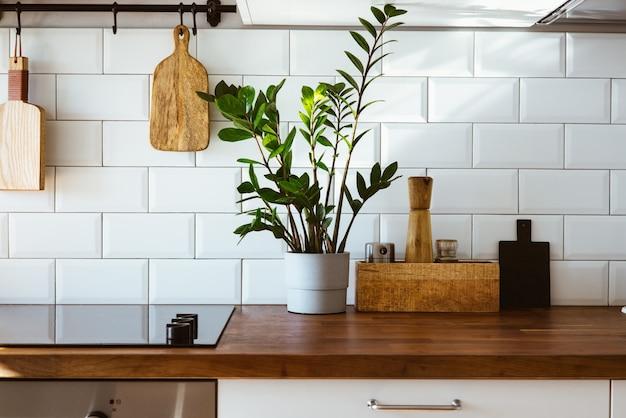 Küchenmessingutensilien kochzubehör hängende küche mit weißer fliesenwand und holztischplattegrüne pflanze auf küchenhintergrund am frühen morgenlicht