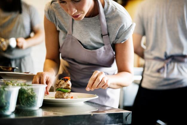 Küchenpersonal, das gekochtes gericht verziert