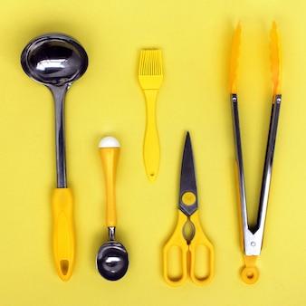 Küchenpfannenzubehör, schere, zange, pinsel, gelber eislöffel auf gelbem grund