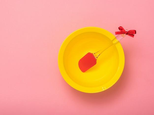 Küchenschaufel in einer gelben schüssel auf rosa hintergrund. küchengeräte auf festlichem hintergrund. flach liegen.