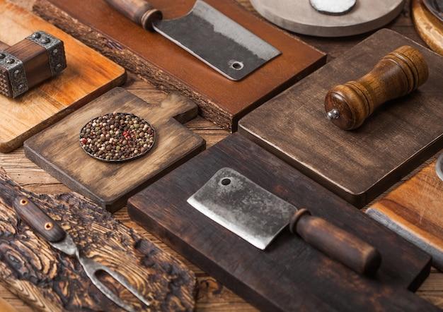 Küchenschneidebretter in verschiedenen größen und formen auf holzhintergrund mit fleischbeilen, gabel und messer und anderen utensilien.