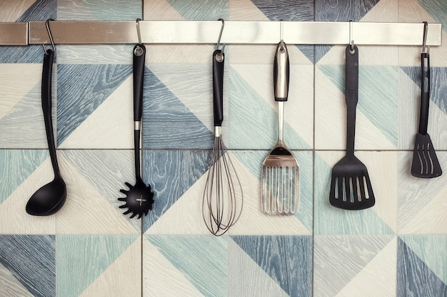 Küchenspatel am geländer an einer gefliesten wand mit geometrischem muster im modernen küchenraum übergeben
