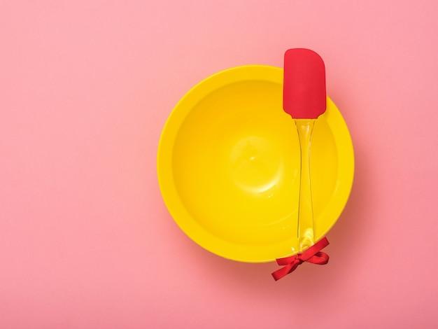 Küchenspatel mit rotem band und gelber schüssel auf rosa hintergrund. küchengeräte auf festlichem hintergrund. flach liegen.