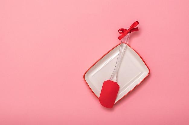 Küchenspatel verziert mit rotem band und weißer schüssel auf rosa hintergrund. küchengeräte auf festlichem hintergrund. flach liegen.
